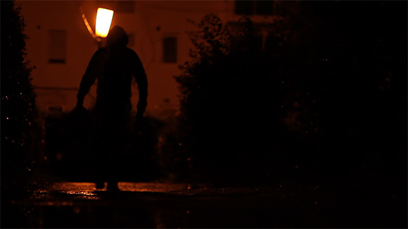 Man Carrying Bag in the Dark