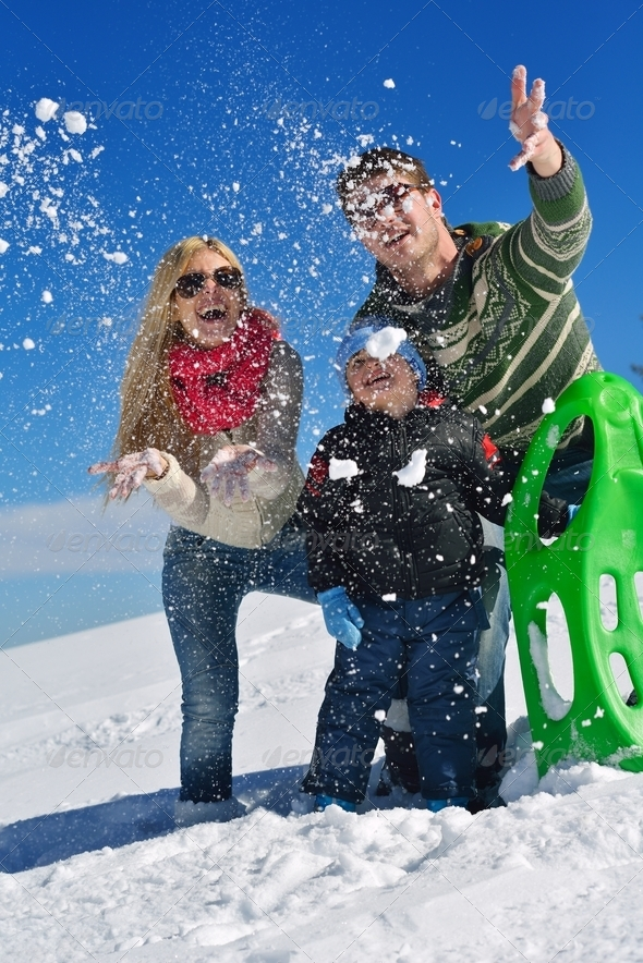 family having fun on fresh snow at winter - Stock Photo - Images