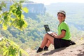 Smiling boy in green t-shirt with a netbook on top of the mounta - PhotoDune Item for Sale