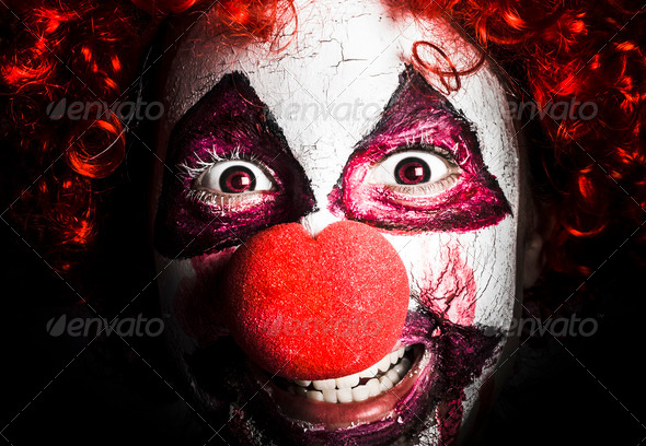 scary and evil clown smiling in dark spooky style - Stock Photo - Images