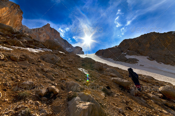 Weary hiker ascent to mountain pass in evening - Stock Photo - Images