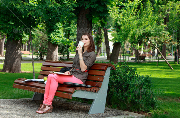 Young Woman Drinking Coffee in a Park  - Stock Photo - Images
