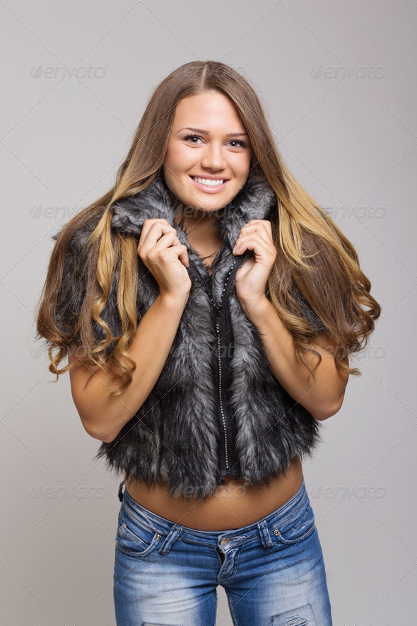 Attractive teenage girl wearing short fur coat smiling - Stock Photo - Images