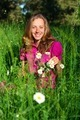 Beautiful smiling woman among the grasses and chamomile