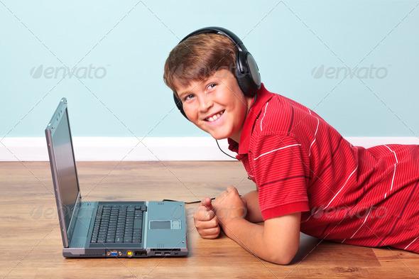 Boy wearing headphones with laptop