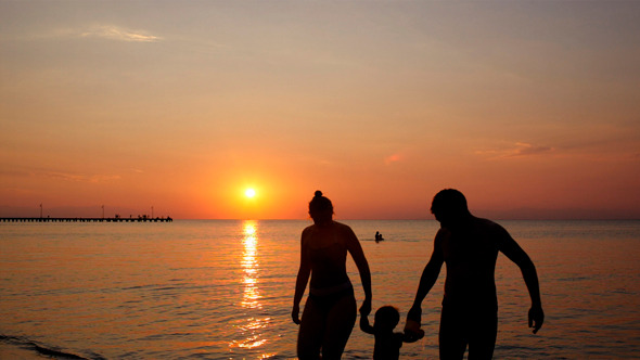 Young Family On The Beach Under A Colourful Sunset