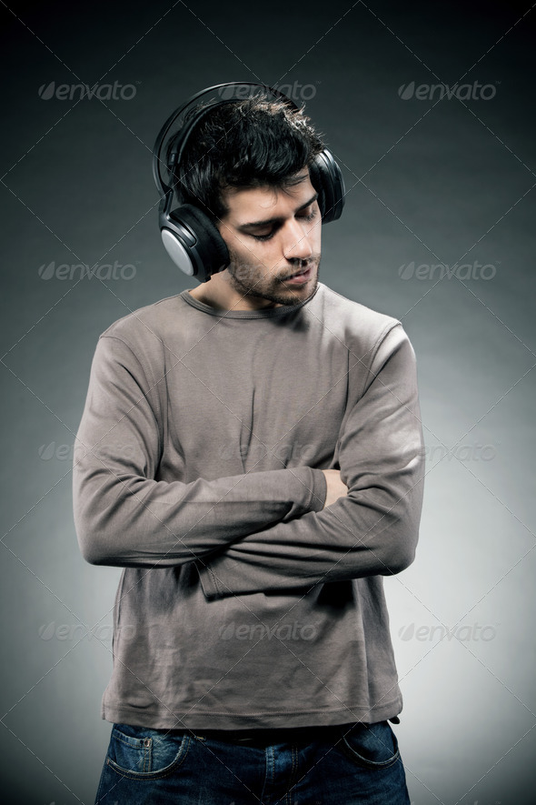 Man is listening to music while wearing headphones - Stock Photo - Images