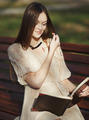 Young cute lady sitting on bench