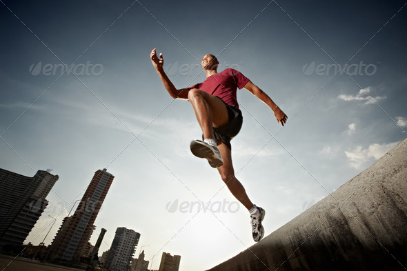 hispanic man running and jumping from a wall - Stock Photo - Images