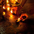 People burning oil lamps as religious ritual in Hindu temple. In