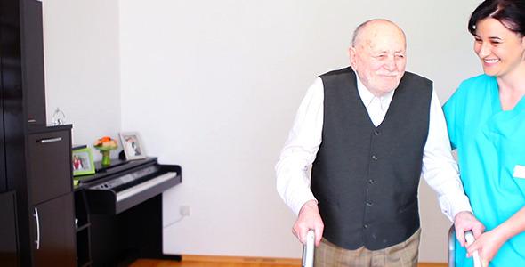Helping Elderly Senior Man Using a Walker