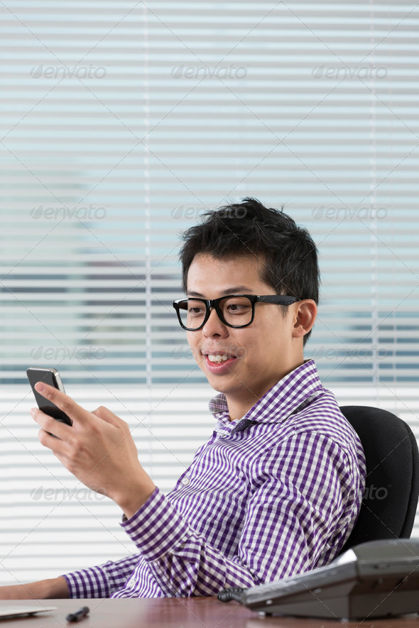 Asian businessman reading his smartphone.