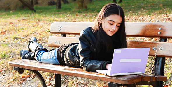 Teenager Sitting On Bench With Laptop 2