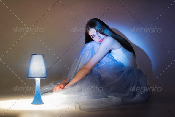 Gorgeous ballet dancer sitting next to lamp - Stock Photo - Images