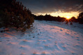 sunbeams over snowy hills at sunset