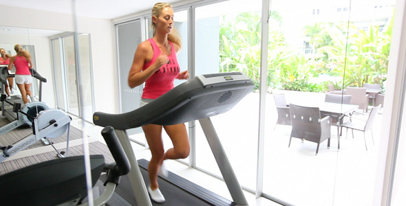 Girl in Gym Running on Treadmill
