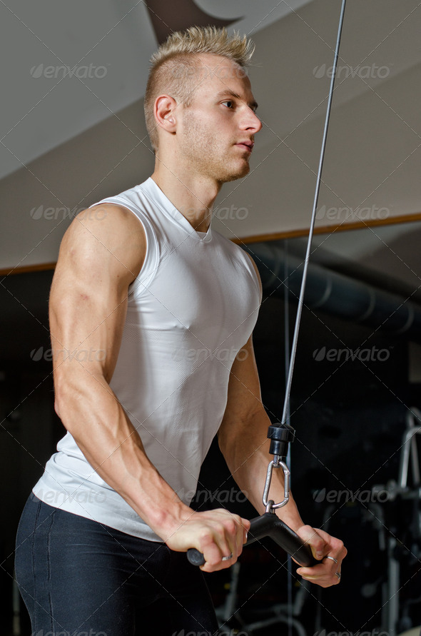 Handsome blond young man exercising triceps on gym equipment - Stock Photo - Images