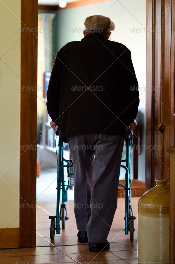 An old disabled elderly man who need additional support to maintain balance or stability while walking use a walker (walking frame) in his house.