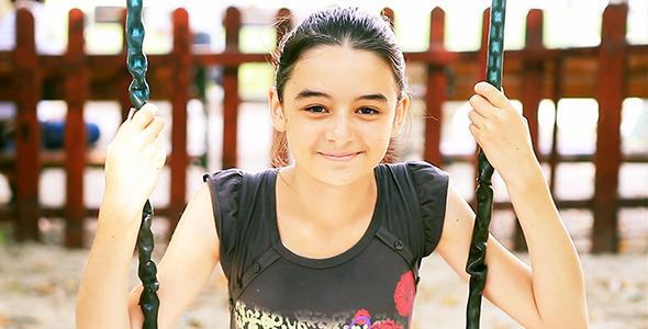 Teenage Girl on Swing Smiling at Camera