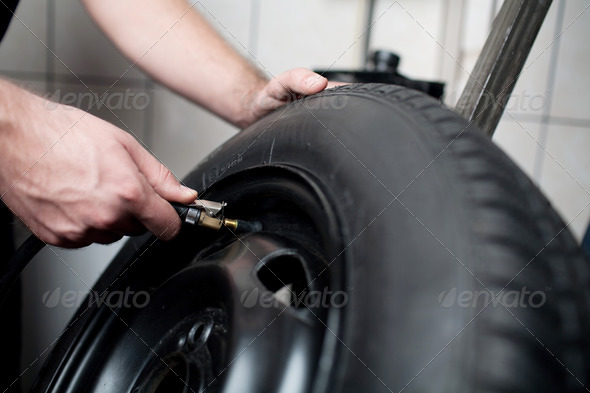 Mechanic filling air into a car tyre. - Stock Photo - Images