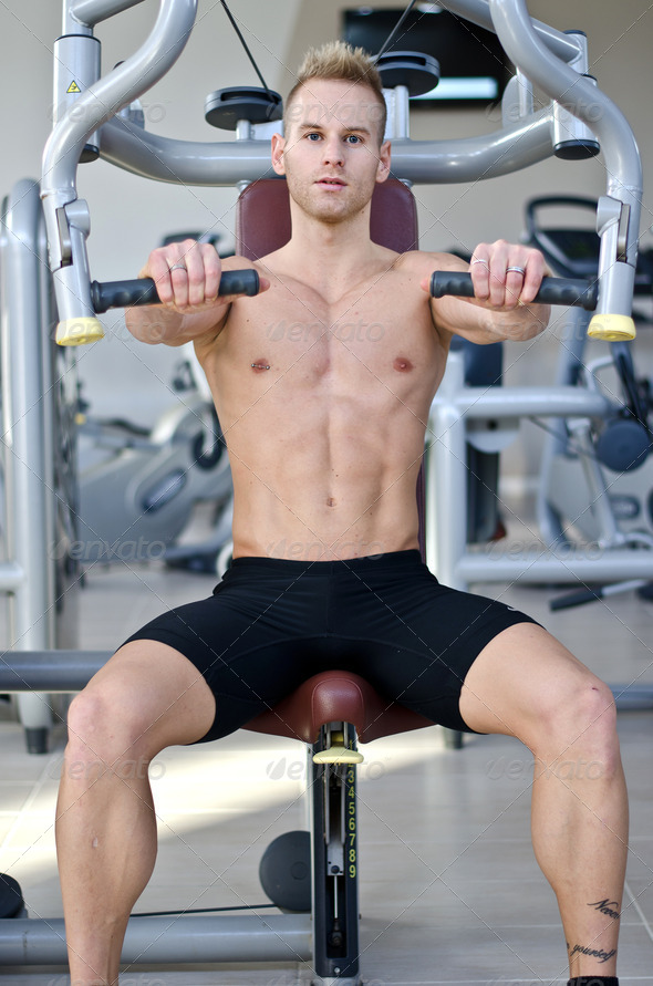 Handsome young man in gym exercising pecs on machine - Stock Photo - Images