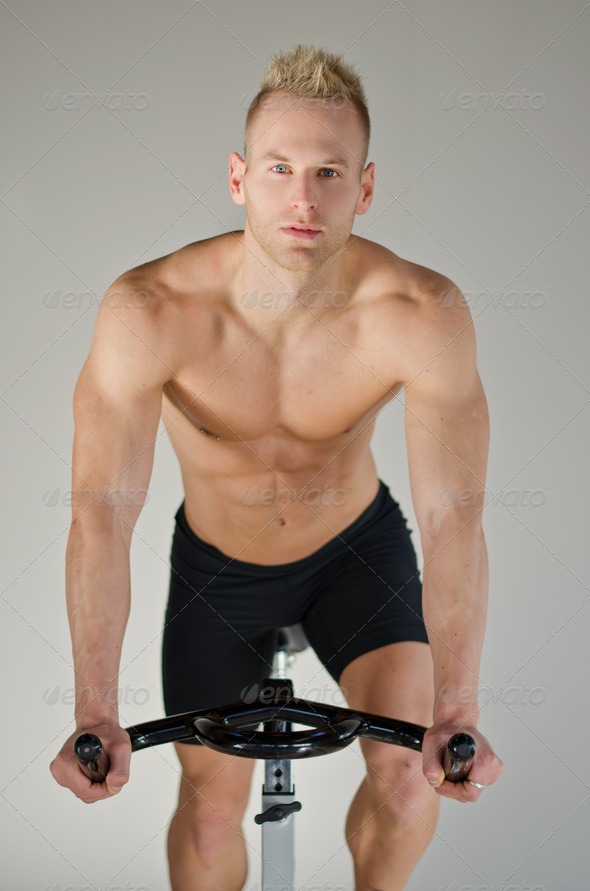 Handsome young man doing spinning on bike - Stock Photo - Images