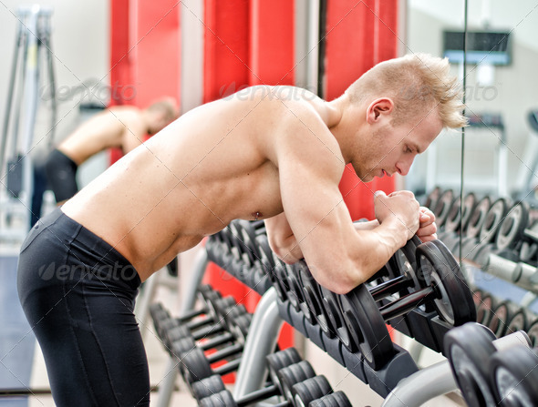 Young man resting on dumbbells rack after workout in gym - Stock Photo - Images
