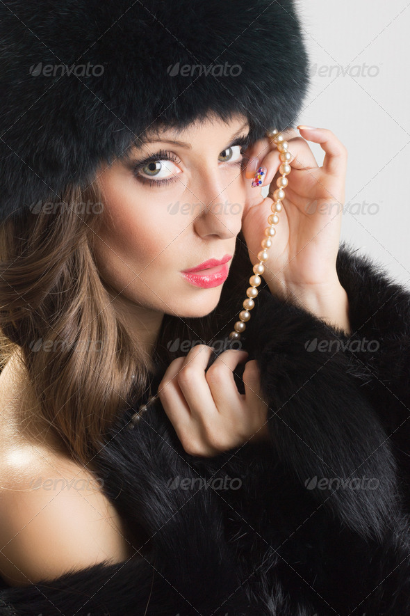 Sensual woman wearing black fur and pearls - Stock Photo - Images