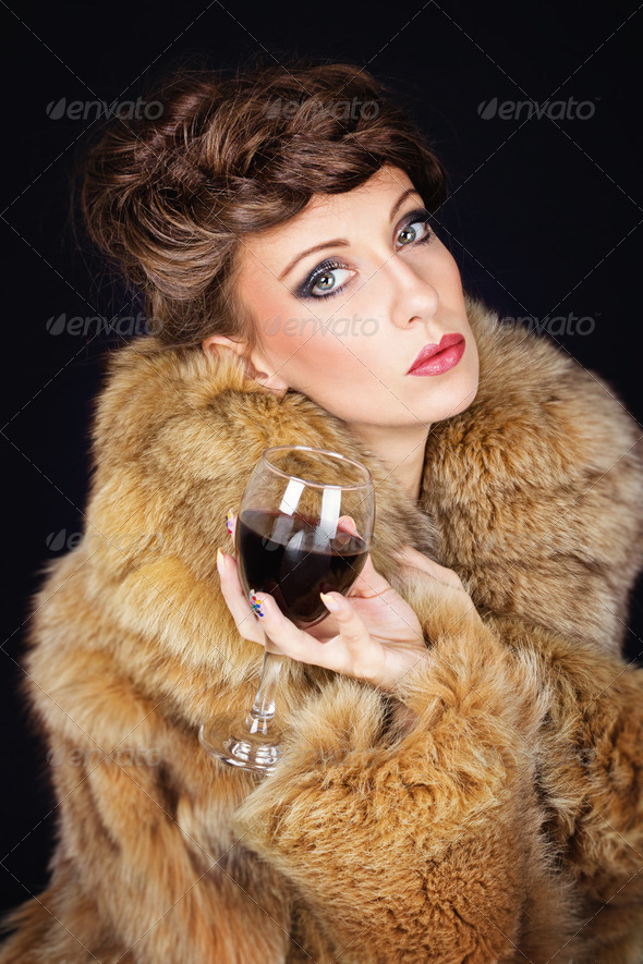 Elegant lady with red wine wearing brown fur coat - Stock Photo - Images