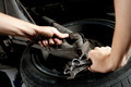 closeup of mechanics hands working below car with wrench - PhotoDune Item for Sale
