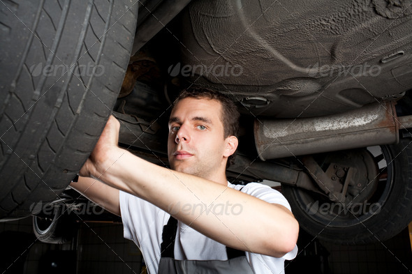 closeup of mechanic working below car with wrench - Stock Photo - Images