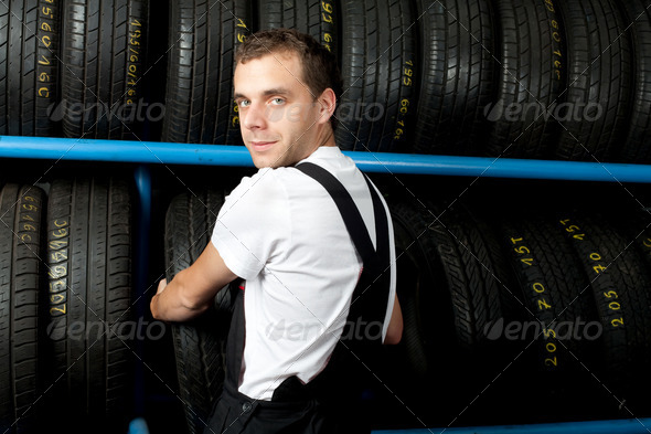 Young mechanic choosing tire in car service - Stock Photo - Images
