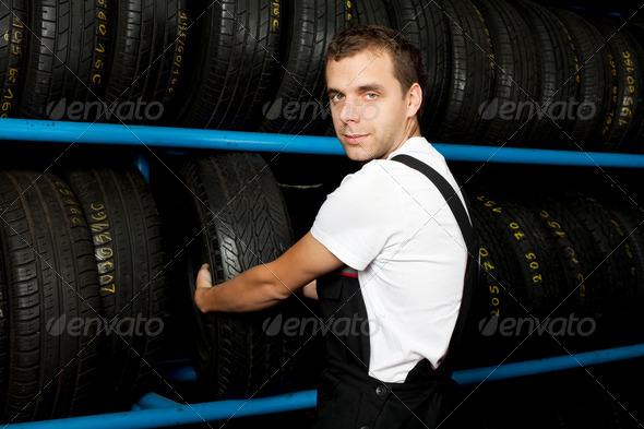 Young mechanic choosing tire in tire store - Stock Photo - Images