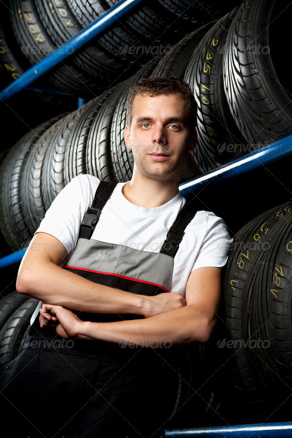 Young mechanic standing next to tire shelves - Stock Photo - Images