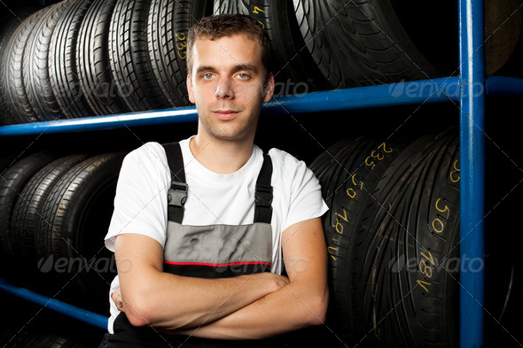 Young mechanic standing next to tire shelves in tire store - Stock Photo - Images
