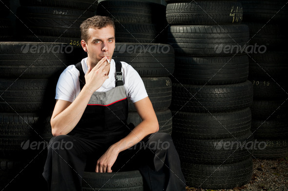 Young mechanic sitting on tire and smoking - Stock Photo - Images