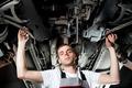Young Mechanic working below car in uniform - PhotoDune Item for Sale
