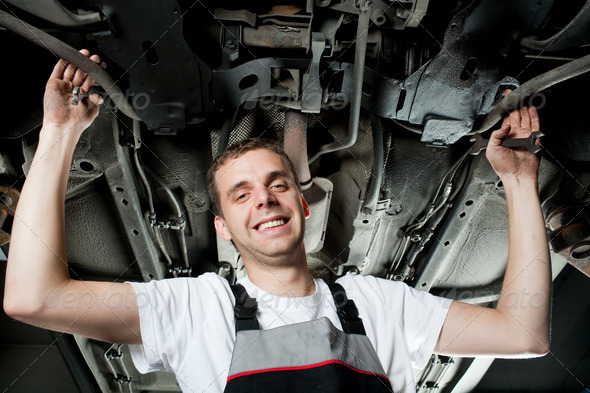 Young mechanic working below the car and smiling - Stock Photo - Images
