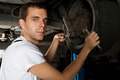 Young Mechanic working below car with wrench - PhotoDune Item for Sale
