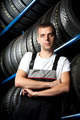 Young mechanic standing next to tire shelves - PhotoDune Item for Sale