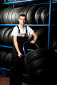 Young mechanic carrying tire in car service - PhotoDune Item for Sale