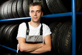 Young mechanic standing next to tire shelves in tire store - PhotoDune Item for Sale