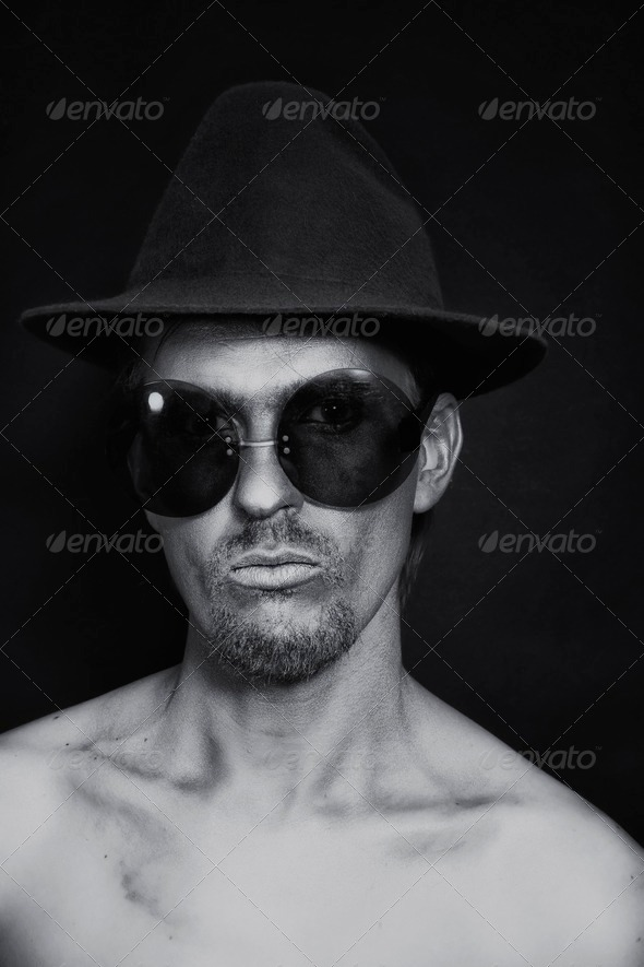 man with silver make-up in hat and sunglasses - Stock Photo - Images