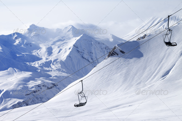 Chair lifts and off-piste slope in haze - Stock Photo - Images