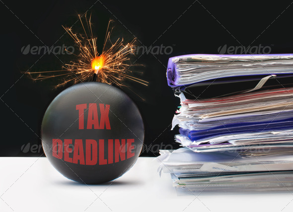 Exploding bomb labeled tax deadline next to a pile of paperwork
