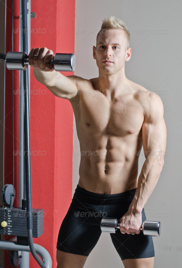 Muscular shirtless young man working out in gym with dumbbells - Stock Photo - Images