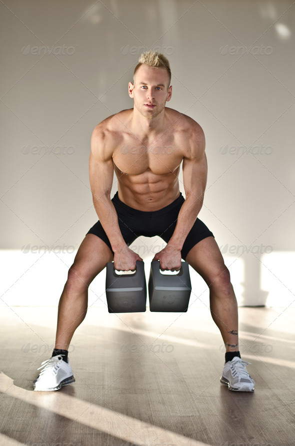 Muscular young man shirtless in gym training with kettlebells - Stock Photo - Images