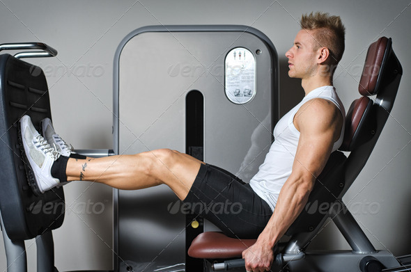 Attractive and fit young man in gym working out legs - Stock Photo - Images