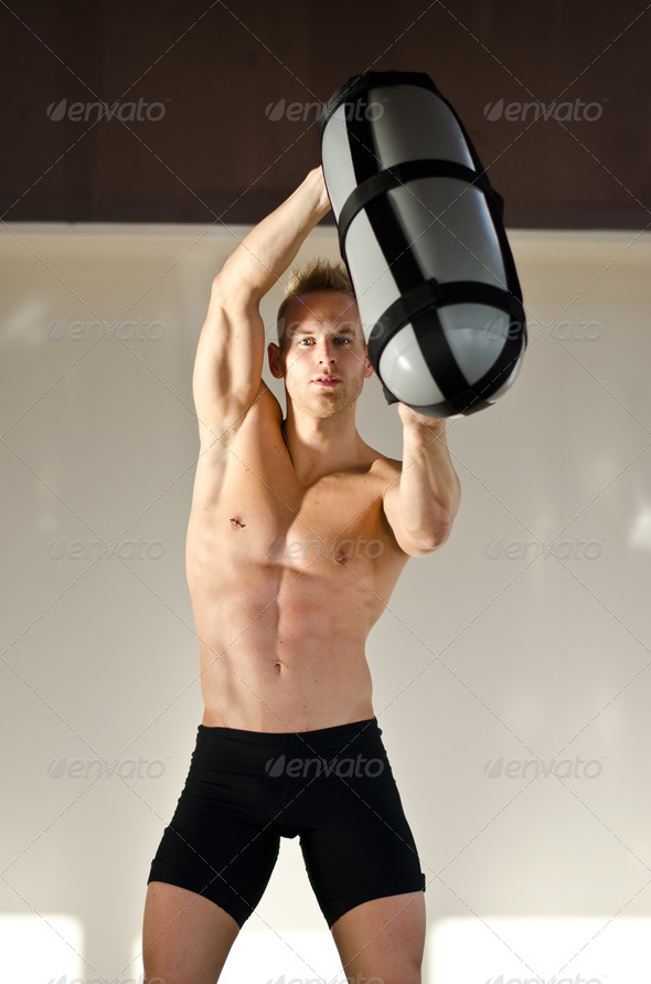Shirtless young man in gym holding water-filled weight in his hands - Stock Photo - Images