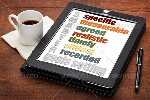 SMARTER (specific, measurable, agreed, realistic, timely, ehtical, recorded) goal setting concept on a digital tablet computer with espresso coffee